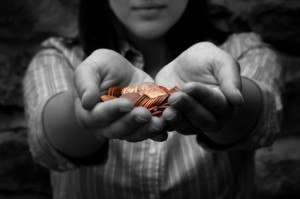 Child Holds Coins in Hands